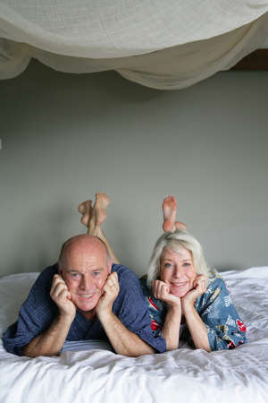50 to 55 years old: Senior couple laying in a bed