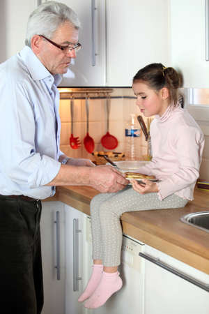 Granddad and granddaughter in the kitchen photo