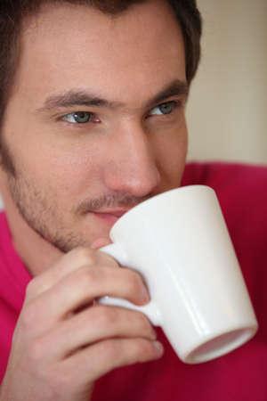 Man drinking from a mug photo