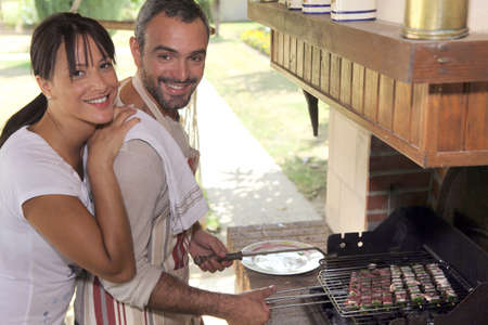 Couple cooking food on outdoor barbecue photo