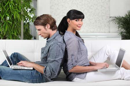 outwork: Pares que se sientan espalda con espalda en un sof� Foto de archivo