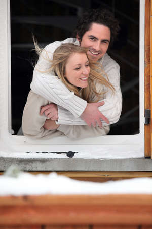 Couple hugging by chalet window photo