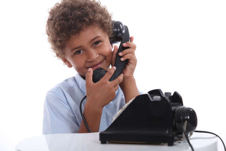 little boy calling with an old telephone photo