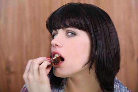 Brunette woman eating slice of chocolate photo
