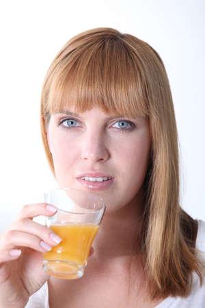 Young woman drinking orange juice photo