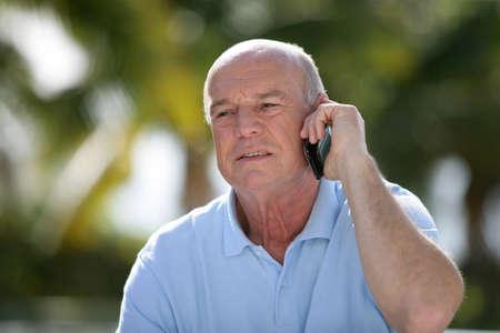 sixty: Senior man using a cellphone