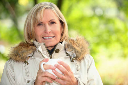 Woman outdoors with a hot drink photo