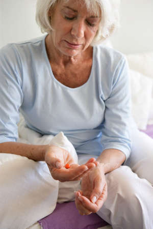 65 70 years: Elderly woman taking a pill