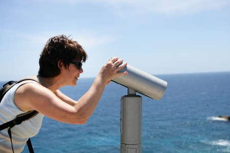 Woman looking through public telescope at the coast photo
