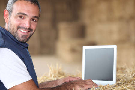 Man using laptop on a farm photo