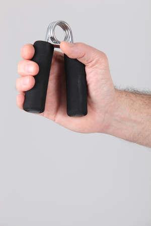 hand gripper: Man using a hand exerciser
