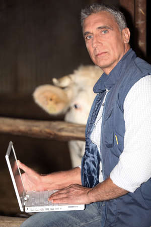 'hide out': Farmer using his laptop in the barn