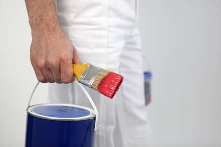 gallon: Decorator holding paint and paint brush