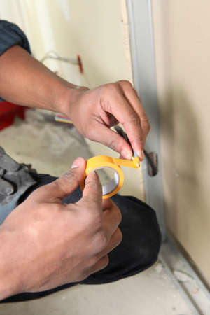 sticky hands: Worker with yellow adhesive tape Stock Photo