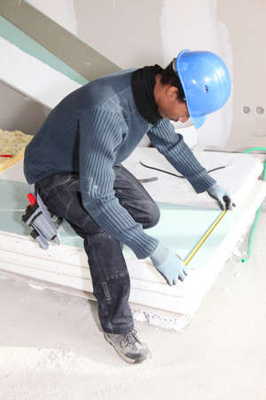 Man measuring insulation boards photo