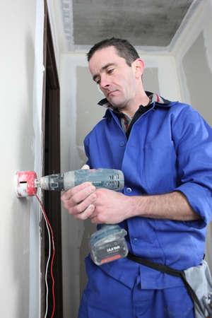 40 years old man: electrician handling drill