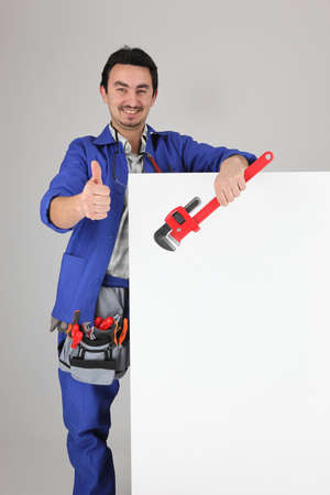 Man with blank board and toolbelt, giving thumbs up photo