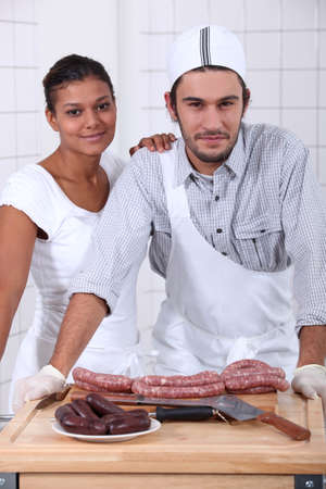veal sausage: Couple working in a butchers Stock Photo