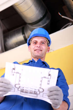 Plumber with the schematics of an air conditioning system photo