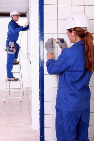jobbing: Electricians working in a tiled room