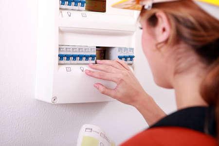 contador electrico: Mujer que controla el medidor de electricidad Foto de archivo