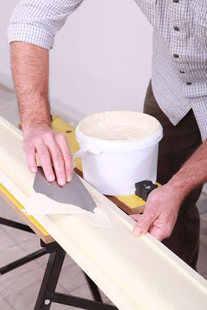 putty: craftsman painting a board Stock Photo