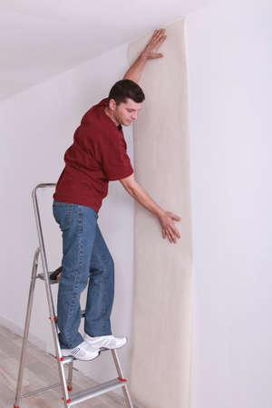 make a paste: Decorator wallpapering Stock Photo