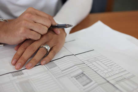 home addition: Married womans hands resting on an architect drawing Stock Photo