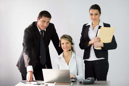 businessteam: Three office workers around a desk Stock Photo