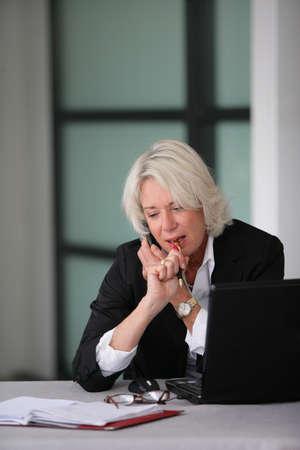 senior businesswoman working at her desk photo