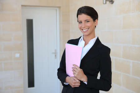 Woman in a suit standing outside a front door photo