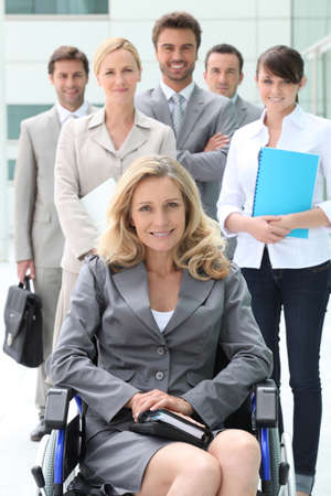 Businesswoman in a wheelchair with her colleagues photo
