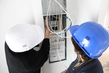 fusebox: Electrician and apprentice repairing fusebox Stock Photo