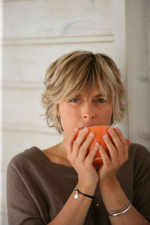 highlighted hair: Woman drinking from a bowl