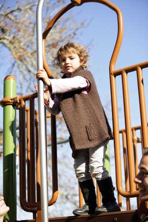 niño escalando: Niña jugando en un parque