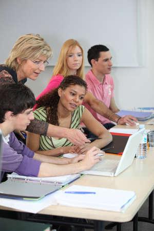 estudiantes adultos: Los estudiantes que buscan en un portátil Foto de archivo