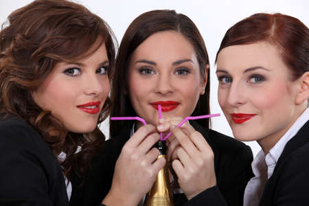 younglady: Three businesswomen drinking champagne from straws