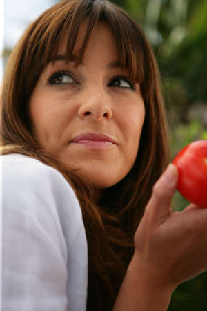 Woman holding a tomato photo