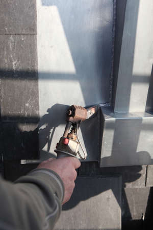 Manual worker using tool to melt lead around window