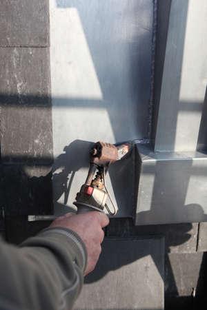 window seal: Manual worker using tool to melt lead around window