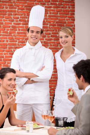 A chef and a waitress working in a restaurant photo