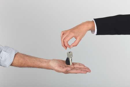passing over: Agent handing over keys Stock Photo