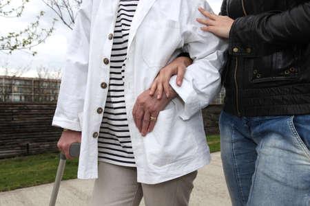 Assistenten helfen, eine ältere Person zu Fuß