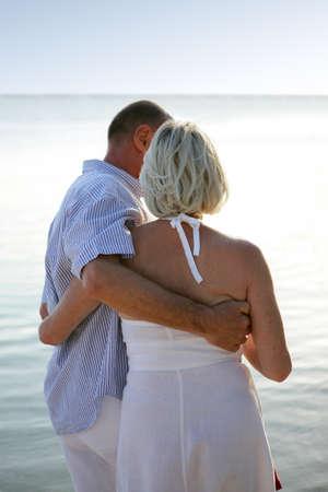 Older couple walking along a beach photo