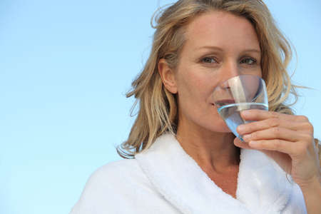 Woman drinking glass water photo