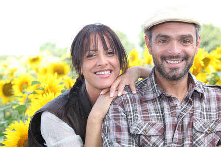 Smiling man and woman in a field of sunflowers photo