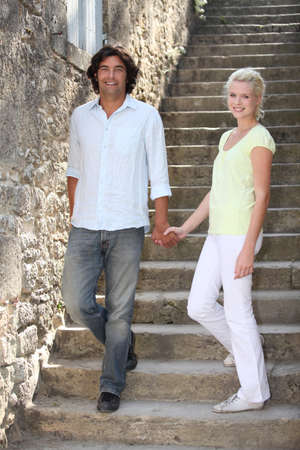 couple descending downstairs in an old village Stock Photo
