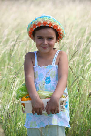 Little girl smiling in a field photo