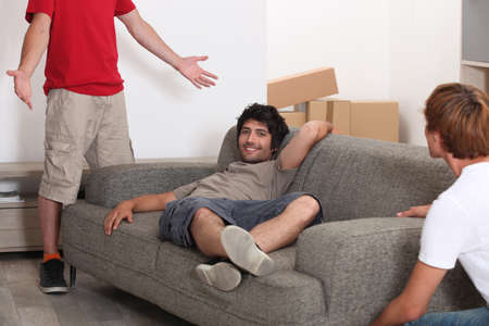 Three lads moving into their new home Stock Photo