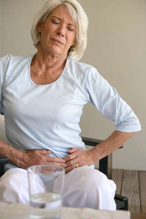 enfermo: Mujer con un dolor de est�mago Foto de archivo